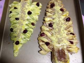 圣诞树面包,发酵完毕后表面刷蛋液,用芝麻和蔓越莓做装饰,烤箱180度预热