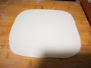 烤里脊肉夹火烧,早晨起床开始做饼:把面团揉光滑,取面团的一半擀成长方形的面饼。
