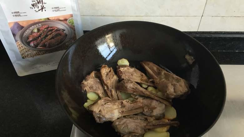 干锅土豆鸭头,倒入解冻的老卤鸭头翻炒半分钟左右;