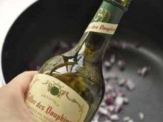 白葡萄酒蒸鲈鱼,锅中放入洋葱碎、水以及白葡萄酒;