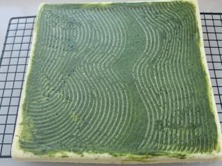 抹茶树桩蛋糕卷,倒扣在烤网上揭去表面油纸晾凉