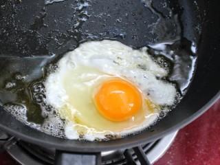 鱼香荷包蛋,锅中放油烧热,磕入鸡蛋后将锅倾斜,这样避免蛋液四处流淌
