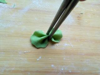 菠菜蝴蝶面,用筷子在中间夹一下,不要太使劲会夹断。剩下的边边角角在揉成面团擀成薄饼,重复上述步骤,做成蝴蝶面……
