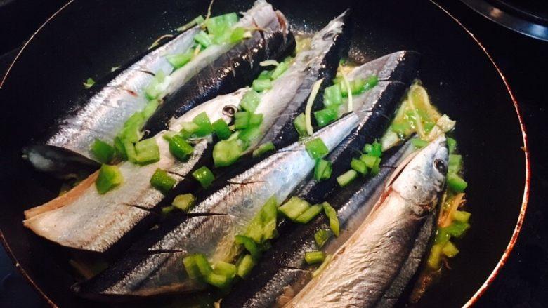 香煎秋刀鱼,将鱼放入锅内,表面再撒一些青椒丁和葱花(鱼有点儿大,切开了😄)