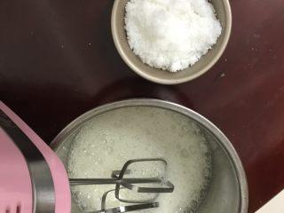 柠檬香戚风纸杯蛋糕,把蛋白里加入几滴柠檬汁,用电动打蛋器高速打至鱼眼状态加入三份之一白砂糖。
