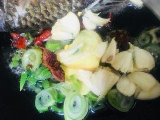 红烧鲫鱼,把鱼推到一边,另外一边放入葱姜蒜小米椒花椒八角一起爆香