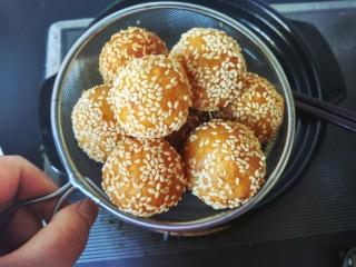 芝麻红薯球,用筷子不停的翻动,炸好后捞出沥油。