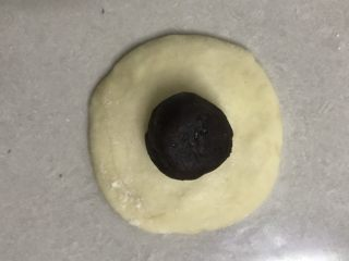 奶香豆沙小餐包,取一个面团,收口朝上用手掌拍打成中间厚边上稍薄的面皮,放上豆沙