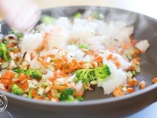 12m+鳕鱼软饭(宝宝辅食),接下来放入之前切好的胡萝卜、西蓝花、香菇丁,翻炒半分钟之后,倒入鳕鱼,再翻炒两分钟~