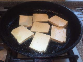 香辣西芹炒豆干,平底锅放烧热,放入豆腐片小火煎。