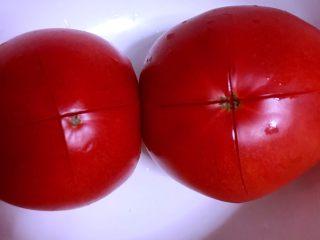 西红柿土豆炖牛腩,煮肉的时间里处理其他食材。西红柿表皮划十字刀用开水烫约两分钟。