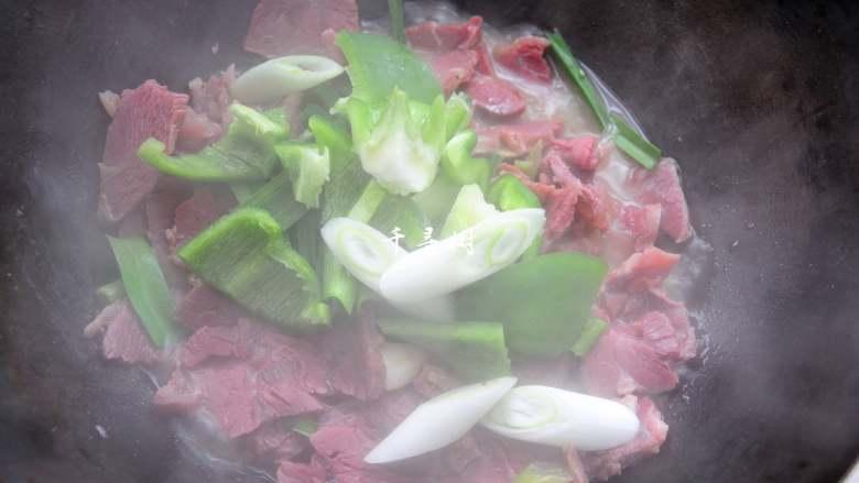 回锅牛肉炒青椒蒜苗 五香牛肉的新吃法,10分钟后拿去锅盖,倒入青椒和葱段及蒜苗叶子,大火收汁。