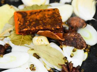 风干羊肉火锅,锅内油热,放生姜 大葱,大蒜,香料,花椒,加一小块火锅底料,小火炒香。