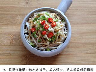 凉拌手撕杏鲍菇,把杏鲍菇中的水充分挤干,放入碗中,把之前兑好的调料汁淋入杏鲍菇中,撒上葱花、蒜末和红椒粒