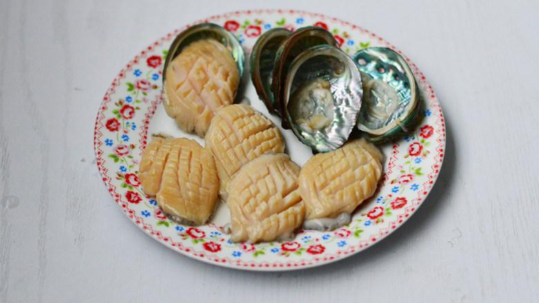 蒜蓉粉丝蒸鲍鱼,用小刀或勺子柄将鲍鱼肉挖出,去除内脏,冲洗干净,在鲍鱼肉上划一些花刀,鲍鱼壳也同样刷洗干净备用