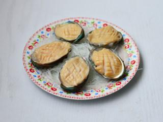 蒜蓉粉丝蒸鲍鱼,将鲍鱼肉放入鲍鱼壳里,摆上摆入粉丝碗中
