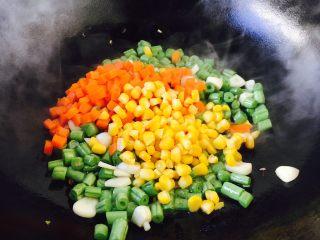 四季豆鲜虾意面,当四季豆煸炒至9成熟放入胡萝卜粒和玉米粒,翻炒均匀。