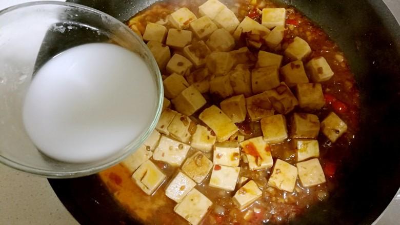 红烧豆腐,然后把生粉水倒入锅中,锅铲背轻推,让豆腐完全的混合均匀,芡汁收干一些。