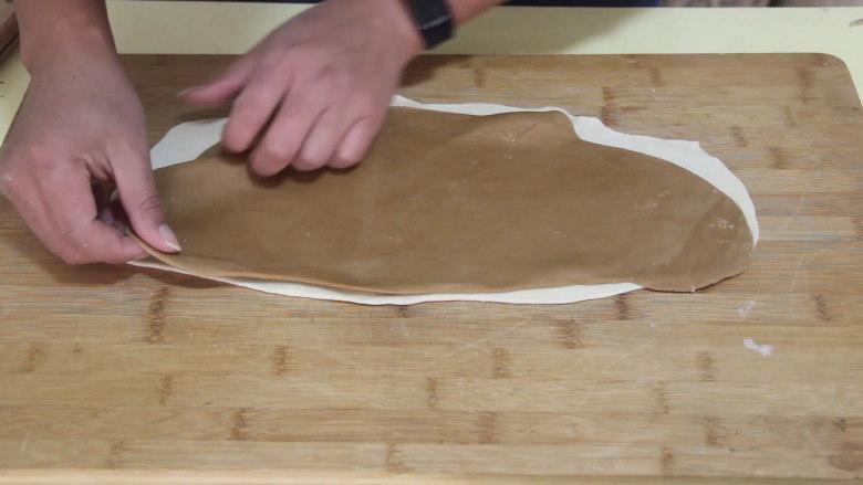 自制猫耳朵,把白色的面饼放下面,红糖水的面饼放上面。铺匀后再用擀面杖擀实