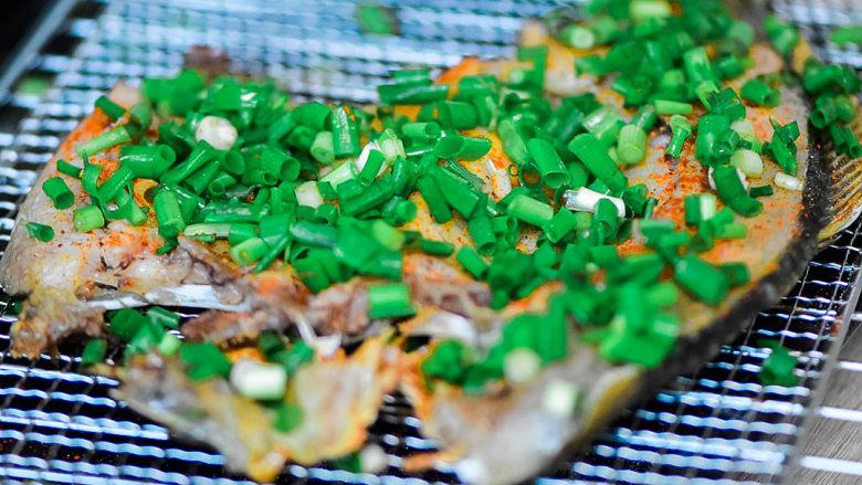 烤鱼,取出后,撒一些辣椒粉,不爱辣的可以不放。把鱼翻过来,满满的撒上葱。