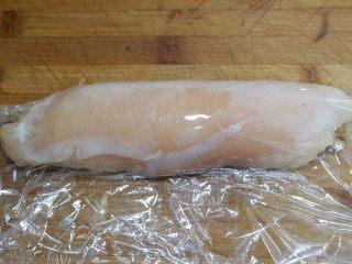 胡萝卜核桃鸡肉卷,卷起来之后,一手握住鸡肉卷,一手拽剩余的保鲜膜,将其包紧