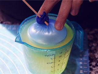 吉丁水晶球—可以吃的水晶球,将我们只做的气球模具,进入到吉利丁液中,此时吉利丁液应该低于手温。按压不下去的时候可以用另一只手帮助按压。