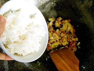 早餐-鸡蛋火腿炒饭,葱的香味出来以后放入米饭,这时候可以把火加大了,中火即可