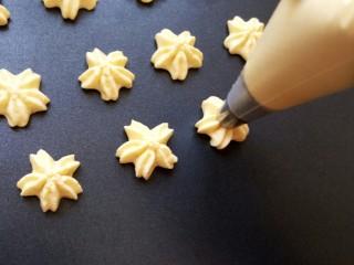 樱花🌸蛋黄小饼干,在不粘烤盘上挤出面糊 如果烤盘很粘需要垫一张油纸防粘