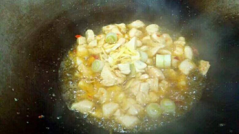 杏鲍菇炒鸡丁,放入葱姜蒜,翻炒均匀。