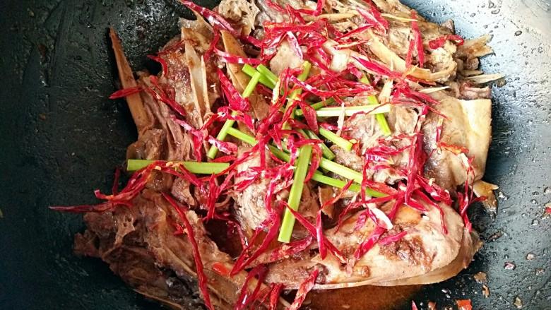 干锅鸭头,加少量的温水,翻炒均匀后,加入香芹和干辣椒丝。