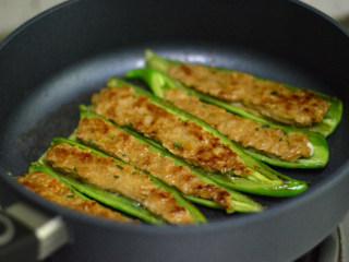 青椒酿肉,锅里放适量油,先将肉朝下,煎至金黄后翻转煎另外一面(翻转的时候小心点,肉容易掉出来)