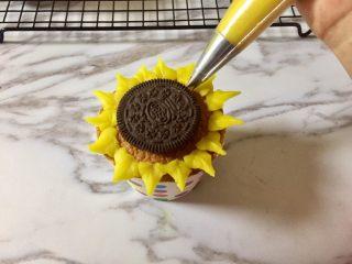 奥利奥向日葵纸杯蛋糕,再在两边花瓣之间的位置,靠近奥利奥饼干的边缘,挤上一圈花瓣。