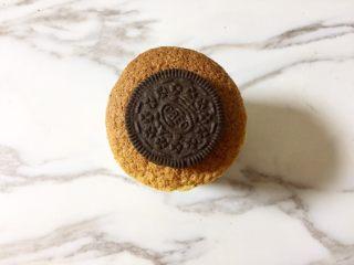 奥利奥向日葵纸杯蛋糕,把奥利奥饼干掰开,用一片饼干就可以,放在蛋糕面的中间,压一压,使其和蛋糕面贴合。