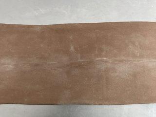 网红脏脏包,将面团擀成长方形,扫去多余的面粉。
