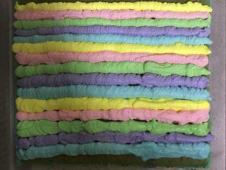 蓝天白云彩虹蛋糕卷 ,先从结尾处,就是上面开始挤奶油,上面预留出3cm空白,先挤出5色比较薄细的奶油线。然后在挤粗的奶油线,按照颜色的顺序依次挤好