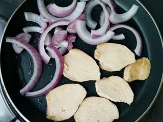 牛油果鸡胸意面,平底锅中刷适量橄榄油,将煮熟的鸡胸切片,和适量的洋葱一起放入锅中,中小火煎一下。