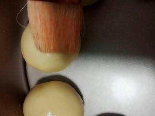 花环小汉堡,用羊毛刷在面团上面刷一点点水,再撒适当的芝麻。
