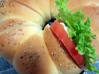 花环小汉堡,然后在每个中间夹入生菜,西红柿,香肠片,再用裱花袋挤入适量的沙拉酱。(也可以抹一些果酱或者肉酱,随个人喜好)