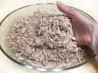 秘制肉松,戴上一次性手套将打散的猪肉块按纹路撕成细条状。