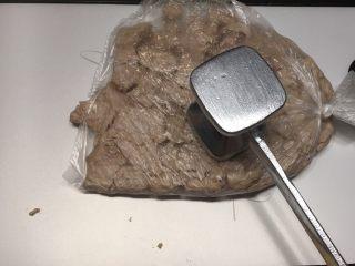 秘制肉松,压熟的猪肉块取出沥干水份放入保鲜膜中,用肉锤敲打,打散肉块。