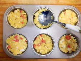 创意料理の马苏里拉奶酪芝士馒丁水果挞,取不沾六连烤盘,用勺子把混合物装进去,并且轻轻压几下