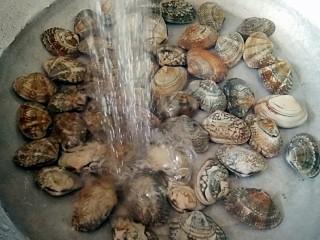 酒蒸蛤蜊――快手复刻美味,买回的花蛤用淡盐水浸泡一下,洗净后沥水捞出装在盘中。
