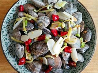 酒蒸蛤蜊――快手复刻美味,将锅中爆出香味的葱姜蒜干辣椒(底油不多的话连同底油一起),均匀撒在蛤蜊上。