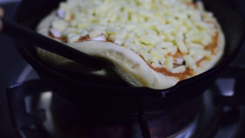 铸铁锅基础披萨,七八分钟后,如果饼底可以轻松揭起来,并且看得到略略发黄,就可以关火。