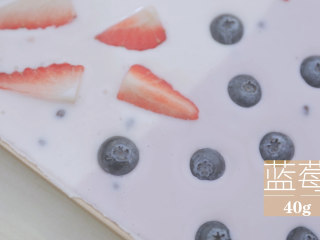 酸奶的2+1种有爱吃法「厨娘物语」,在草莓酸奶部分装饰80g草莓块,蓝莓酸奶部分装饰40g蓝莓,表面撒上开心果碎。
