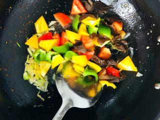 彩椒炒鸡丁,依次加入彩椒和木耳翻炒,加入少许水略煮