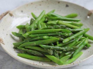 油淋芦笋,将芦笋捞出放入冷水中过凉,沥水后放入盘中。