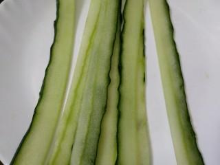 菠萝咖喱饭,黄瓜提前浸泡淡盐水20分钟去除农药,用刮皮器将黄瓜刮成长片,也切成食指宽的条状。