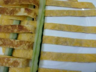 菠萝咖喱饭,大盘子上抹少许植物油,将鸡蛋条和黄瓜条用编花篮的方法编织在一起,如图。