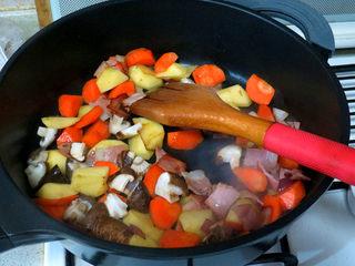 浓郁味香的【培根奶油炖菜】,土豆红萝卜块入锅翻炒,再加入香菇炒至半熟